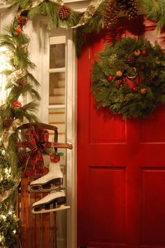 Red front door with Christmas wreath and a sled with skates hanging from it.