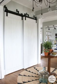 inspiredbycharm.com - painted barn doors - doors and track system from Rustica Hardware, bypass door system