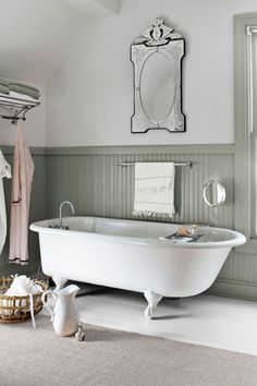 Conventional wisdom dictates white on wainscoting and color above, but the owner of this Montana farmhouse flipped that combination by painting the trim in her master bathroom a (custom-blended) mossy green and the upper walls ivory.