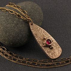 """Delicate and regal! This unique long shield pendant features a gorgeous 8mm lab ruby cabochon and stunning """"Goldie Bronze"""" metal clay. The surface is highlighted with a dainty vine pattern, and the luminous ruby is set in a hand made bezel form accented with bronze granulation."""