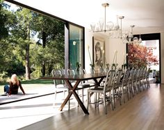 Frog Hill Designs Blog Dinner for 20?  No problem. Love the #nanadoors that open this dining room seamlessly to the outside.  Defines bringing the outside in.  Love the metal utilitarian chairs and light fixtures.  #largediningtable #metalkitchenchairs