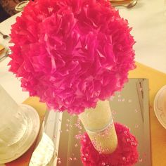Inexpensive centerpieces made from dollar store vases with glittery fabric hot glued on and styrofoam balls with tissue paper flowers. Very time consuming but definitely worth it!