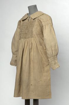"1860-1869 British Smock at the Victoria and Albert Museum, London - From the curators' comments: ""This traditional English garment is of a type worn by country men and boys, agricultural workers in particular, until the late nineteenth century, and often embroidered with symbols or patterns indicative of their work. Smocks are made from squares and rectangles of fabric, which makes a paper pattern un-necessary in their construction and eliminates wasting fabric in cutting curved facings…"