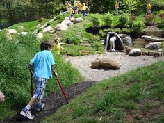 Natural play area with rock cave feature and embankment slide.