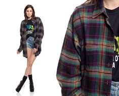 cut off denim shorts, with distressed detail, 90s aesthetic, worn with a black oversized t-shirt, partially tucked in, under a retro flannel shirt