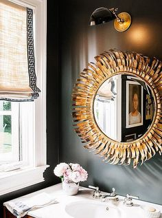 Love the combination of the bold oversized sunburst mirror with the matte black wall paint.