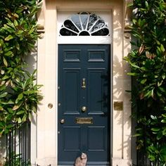 Love the design and trim around this door!  And, although I am not crazy about blue, this blue door, with the cream trim & green foliage, seems to work!