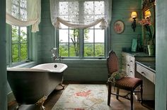Rustic Bathroom with Green Wooden Wall containing: Dark Clawfoot Tub with Floral Patterned Rug also Classic Vanity Light plus Wooden Chair together with Stone Vanity Top with Transparent Roman Shade also Floor Mount Tub Faucet plus Wood Flooring