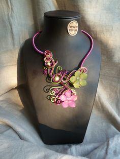 Collier aluminium rose et vert - FLORAL  Collier en fil aluminium rose fuchsia et vert pomme.   Composé de perles magiques et deus fleurs effet glacé.   Idéal pour apporter féminité et gaieté à votre décolleté, ce collier saura se faire remarquer.   Les deux fleurs donnent quant à elle une touche de fraîcheur.   Les deux côtés se rassemblent par l'avant.