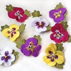 Pansy brooches hand embroidered felt pansy brooch available in purple white yellow and fuchsia pink floral gift viola flowersPansies are such adorable flowers, I couldnt resist making these little felt brooch versions! My pansy brooches are available Felt Crafts Diy, Felt Diy, Fabric Crafts, Felt Applique, Crewel Embroidery, Embroidery Patterns, Hungarian Embroidery, Embroidery Hoops, Embroidery Jewelry
