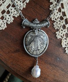 This necklace is made of Fine Silver .999 It features a gorgeous fossilized sand dollar as well as a baroque pearl. www.nasartisanjewelry.com Baroque Pearls, Handmade Silver, Artisan Jewelry, Pocket Watch, Pendant Necklace, Accessories, Drop Necklace, Pocket Watches, Jewelry Accessories