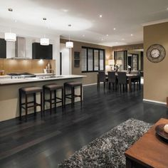 Wonderful Kitchen and Dining Room with Long Island and Dark Dining Table on Grey Hardwood Floors