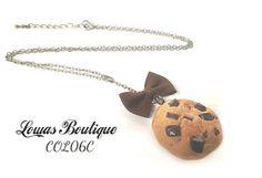 Collier Cookie Ce collier est constitué d'un cookie en fimo avec un petit noeud en tissu, le tout monté sur une chaine en bronze.   Chaine d'extension inclus. Fermoir mousqueton inclus. Dimension: 58,5 cm