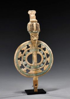 "Veracruz Pottery Platform Slide Whistle : Pre-Columbian, Gulf Coast Mexico, ca. 600 – 900 CE. With a sliding ball inside which modulates the tone when the instrument is tipped. Above the bore is a sculpted figure wearing an elaborate headdress. The head and the pierced geometric platform are painted in polychrome. 12-1/2"" L."