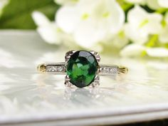 What an elegant engagement ring this is with such lovely classic details and design! The center stone was deemed a green tourmaline by a