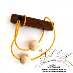 El objetivo de este rompecabezas es juntar las dos bolas en el mismo lado del cordel. Precio: 8,10 € www.artesania-alla.es