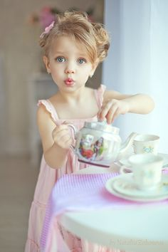 Little girl in pink dress having a tea party by herself.
