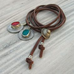 A simple, casual and cool necklace with tribal Gypsy charms clustered on leather. Completely adjustable and perfect for this years layered jewelry look. It also looks great as a bracelet, wrapped several times around your wrist.    There are two vintage coins from the Middle East, they were made into charms by the Kuchi Gypsy people.    The largest coin is set with a transparent red glass cabochon. It's 28 mm in diameter or just a bit over an inch not including the bail.    Next to it is a…