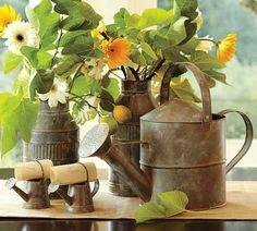 déco de terrasse originale avec arrosoirs métalliques en tant que vases