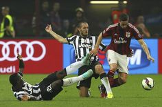 Fernando Torres (R) of AC Milan is challenged by Giorgio Chiellini (C) and Kwadwo Asamoah (L) of Juventus FC during the Serie A match between AC Milan and Juventus FC at Stadio Giuseppe Meazza on September 20, 2014 in Milan, Italy.