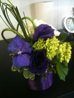 Modern flower arrangement with looped grasses, hydrangea, and purple vanda orchids.   www.helenolivia.com