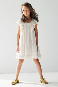 The Juliet Girls Dress by Nellystella is a sweet A-line dress with flutter sleeves and pleated detailing on the front. 95% cotton, 5% lurex, cotton lined.