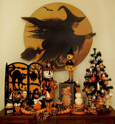 A Boardwalk Witch flying through the Moon hanging board anchors this Debra Schoch Halloween figural display. Don't you love the mini Halloween ornament tree on the right!?