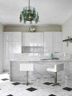 An all white kitchen makes a perfect backdrop for unique lighting.