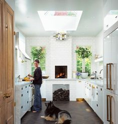 Homeowner Sasha Seymour's kitchen is a true showpiece with a fireplace oven and double fridges. Light pours in from an oversized skylight, illuminating the brass hardware. As Sasha prepares dinner, her dog Cleo happily pads around on herringbone wood floors that look as though they belong in a pre-war New York apartment or Parisian pied-à-terre.