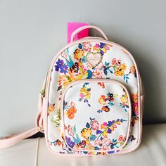BETSEY JOHNSON *MINI FLORAL BACKPACK* BETSY JOHNSON  *MINI FLORAL BACKPACK*   BLUSH ENAMEL HEART WITH GOLDTONE HARDWARE  *AUTHENTIC*  MSRP $88  FEATURES:  Large interior compartment One zip pocket, Cushioned straps Zip around closure Goldtone detail and hardware Pebble leather blush bottom, no feet Betsey Johnson Bags