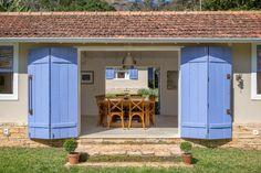 Este é o espaço de convívio da família no sítio Marigold, com projeto do arquiteto André Luque. As portas do tipo camarão, pintadas em um suave azul-lavanda, se abrem para os visitantes que são recebidos pela grande mesa de refeições para 12 pessoas, iluminada por pendentes com ares industriais