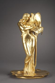 An Art nouveau candlestick depicting 'Femme à l'iris sur une feuille de nénuphar' (Woman with iris on a water lily leaf) by the French sculptor Alexandre Clerget (1856-1931). The...