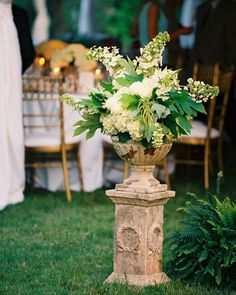Large urns overflowing with floral arrangements flanked the entrance to the reception tent at this real wedding.