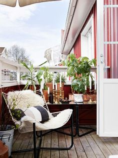 Simple Nordic balcony with table full of candles in bronze holders and lush potted plants for an atmosphere of luxury.