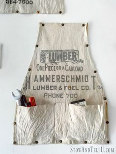 Put that old work apron to use as hanging storage. Clever organizing idea for your tool shop, work shop, craft room, hobby shed. Supplies: decorative nails and a hammer.