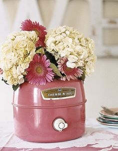 Most any container can make a distinctive vase, no matter its original purpose. A cluster of hydrangeas and Gerbera daisies complement the deep shade of pink on this unique vessel.