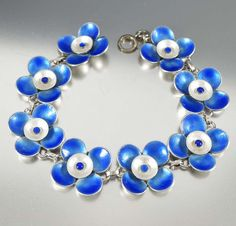 Exquisite triple layer blue and white enamel flowers glow in this English Arts and Crafts bracelet by Bernard Instone, circa 1930. 30 grams of sterling silver coil around the wrist with delightful blu