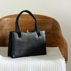 Another beautiful, 1950s black handbag with gold detailing and gold clasped closure in excellent vintage condition. I love how structured this piece