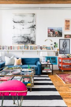 Loft living room with high ceilings, a blue velvet sofa, large art, a wall of books, and a large stripped area rug