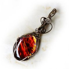 Orange Paua Shell Wire Wrapped Pendant Antiqued bronze wire wrapping highlights a beautiful orange paua cabochon. The shell is iridescent, with touches of red and gold. Handmade wire wrap. One of a kind. Only 1 available.