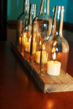cut wine bottles used as cloches for candles and a wooden board to hold them all