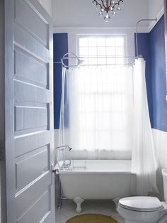 A white bathroom with blue walls is filled with a freestanding, clawfoot tub, which has a canopy shower curtain. A delicate crystal chandelier also hangs in the bathroom.