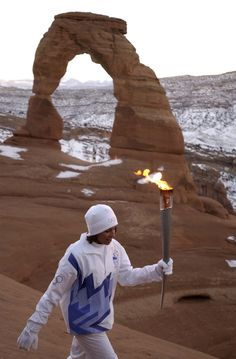 Stephanie Laree Spann carrying the Olympic torch from Delicate Arch in Arches National Park.