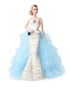 Mattel Barbie doll dressed in Oscar de la Renta's timeless and feminine style for her wedding day. Strapless, lace wedding dress with sparkling brooch and tiered, tulle train. Cluster earrings, a chig