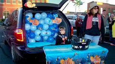 Marilyn Halstead / The Southern Jenny Hertter and Louie hand out candy from the back of a van decorated like an ocean of fish during Walnut Street Baptist Church Trunk