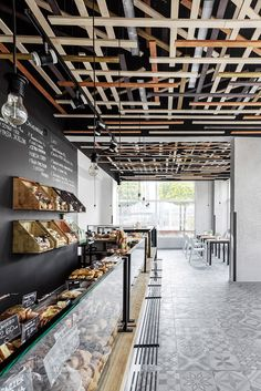 Lovely combination of edison lights, wood and concrete colour statement tiles - Gallery of Przystanek Piekarnia Bakery / Five Cell - 1