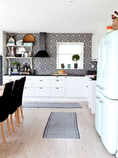 Black moroccan backsplash, open shelves and retro refrigerators