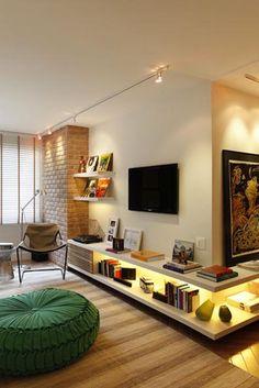 O volume de tijolinhos pode ser uma lareira e em frente a ela um espaço de leitura com uma poltrona com apoio de pés, uma manta, uma mesinha baixa de apoio, para o chá quente, o vinho e para completar o cenário uma luminária de piso.