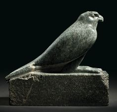 AN EGYPTIAN GRANODIORITE FALCON  LATE PERIOD-PTOLEMAIC PERIOD, CIRCA 4TH CENTURY B.C.  Depicted standing on an integral rectagular plinth, finely modelled and executed, the head with prominent eyes and clearly defined facial markings, and characteristic short, sharp beak, with long talons, the wings held close to the body, the tips crossed over behind, the plinth shaped to accommodate the wing tips and tail feathers