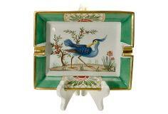 "This is a collectible Hermès ashtray with 24K goldleaf over fine china. Pre-copyright piece with hand-painted blue bird and two cigar holders, stamped ""Hermès-Paris"" and ""Made in France"" beneath green border."